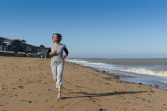 Femme mûre courant sur la plage Image libre de droits