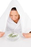 Femme mûre cuisant le visage à la vapeur avec le romarin dans la cuvette de l'eau Photos stock