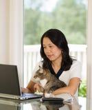 Femme mûre détendant avec son chat tout en travaillant à la maison Photos stock