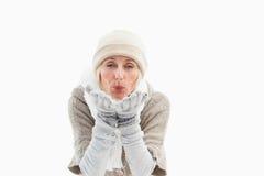 Femme mûre dans des vêtements d'hiver soufflant le baiser photographie stock libre de droits