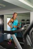 Femme mûre de forme physique s'exerçant sur un tapis roulant photo stock