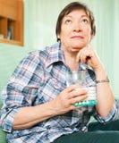 Femme mûre de pensée avec des pilules et verre de l'eau Photos libres de droits