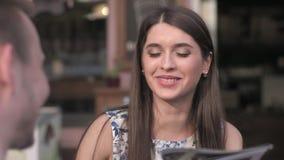 Femme mûre de sourire appréciant une tasse de café à un café extérieur avec un ami en ville banque de vidéos
