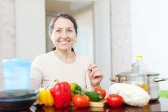 Femme mûre de sourire avec des légumes images stock