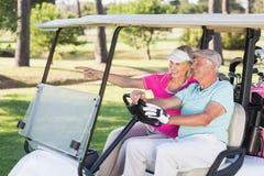 Femme mûre de sourire de golfeur montrant à l'homme Photo stock
