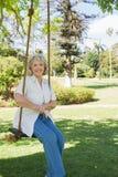 Femme mûre de sourire s'asseyant sur l'oscillation en parc Image libre de droits