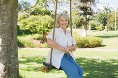 Femme mûre de sourire s'asseyant sur l'oscillation en parc Images libres de droits
