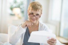 Femme mûre de sourire tenant l'enveloppe photos stock