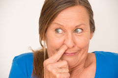 Femme mûre drôle bloquant le nez Images libres de droits