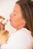Femme mûre embrassant des animaux familiers de cobaye Photographie stock