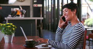 Femme mûre en café travaillant à l'ordinateur portable et au téléphone de réponse banque de vidéos