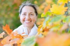 Femme mûre en stationnement d'automne Photographie stock libre de droits