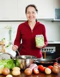 Femme mûre faisant cuire la soupe avec du riz Photographie stock