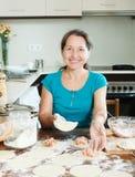 Femme mûre faisant des boulettes à partir de la viande Images stock