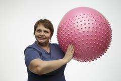 Femme mûre faisant des exercices avec la boule rose dans le studio Photos stock