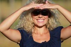 Femme mûre heureuse avec des lunettes de soleil Images stock