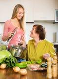 Femme mûre heureuse avec la fille adulte faisant cuire ensemble Image stock