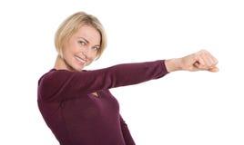 Femme mûre heureuse d'isolement avec le bras et le poing tendus. Images stock