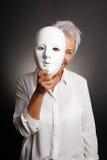 Femme mûre heureuse jetant un coup d'oeil par derrière le masque Images stock
