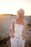 Femme mûre heureuse marchant sur la plage Photos libres de droits
