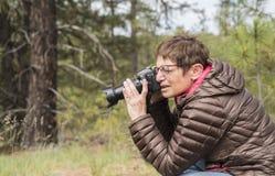 Femme mûre heureuse prenant des photos avec un appareil-photo de Digital DSLR Images libres de droits