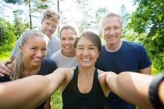 Femme mûre heureuse prenant Selfie avec des amis dans la forêt Photos stock
