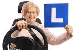 Femme mûre heureuse s'asseyant dans un siège de voiture et tenant un L-signe Images libres de droits