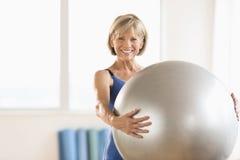 Femme mûre heureuse tenant la boule de yoga à la maison image stock