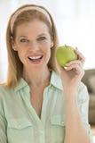 Femme mûre heureuse tenant mamie Smith Apple At Home Photographie stock libre de droits
