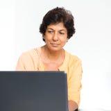 Femme mûre indienne à l'aide de l'ordinateur portable photos stock