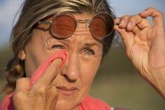 Femme mûre inquiétée avec des lunettes de soleil Photo stock