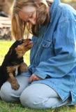 Femme mûre jouant avec le chiot mignon affectueux Images stock