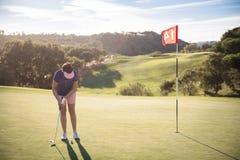 Femme mûre jouant le golf avec le club de putter Images stock