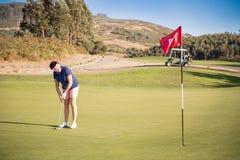 Femme mûre jouant le golf avec le club de putter Photos stock