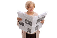 Femme mûre lisant un journal Image stock