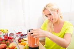 Femme mûre mélangeant un smoothie Images stock