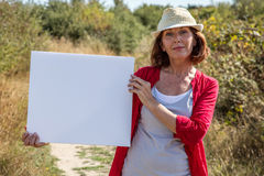 Femme mûre magnifique souriant montrant sa recherche sur le signe dehors Photos stock