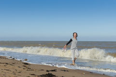 Femme mûre marchant en mer Image stock