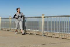 Femme mûre marchant pour presser par la plage Images stock