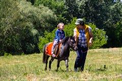 Femme mûre menant un poney avec un tour de fille Photos stock