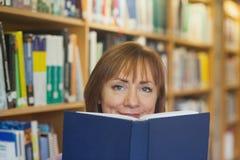 Femme mûre paisible tenant un livre dans une bibliothèque Photographie stock libre de droits