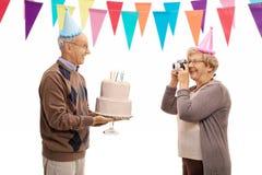 Femme mûre prenant la photo de l'homme plus âgé célébrant sa naissance Images stock