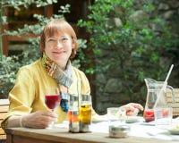 Femme mûre prenant le déjeuner dans le restaurant Photographie stock
