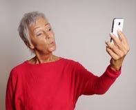 Femme mûre prenant un selfie de smartphone avec le visage de canard Images libres de droits