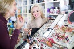 Femme mûre regardant des étagères avec des produits photos stock