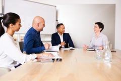 Femme mûre riant de la réunion d'affaires avec trois autres personnes image stock