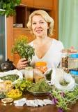 Femme mûre s'asseyant à la table avec les herbes médicinales photos stock