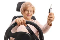 Femme mûre s'asseyant dans le siège de voiture et tenant la clé de voiture Photos stock