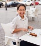 Femme mûre s'asseyant en café Photo stock