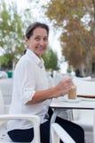 Femme mûre s'asseyant en café Image libre de droits